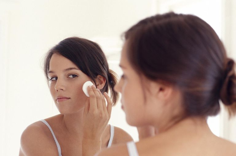 Young woman applying makeup -- is your makeup causing pimples?