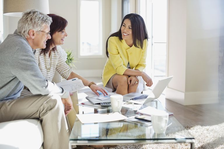 couple talking to real estate agent at coffee table