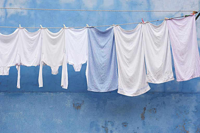 While laundry hangs in front of a pale blue wall