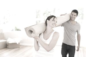 man and woman carrying rug in house