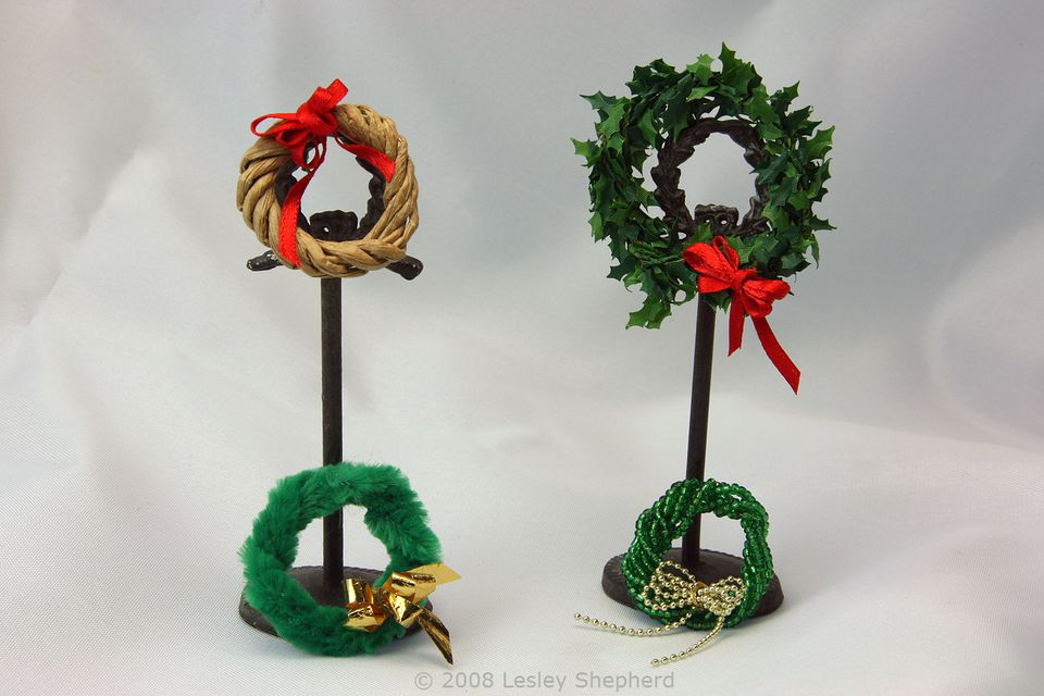 Four miniature Christmas wreaths made from different wire trims decorated with miniature bows.