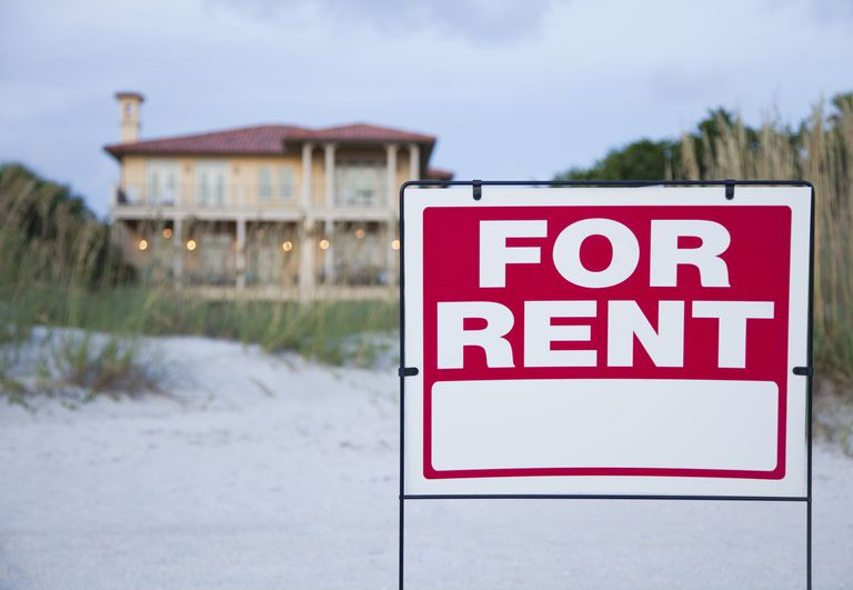 for rent sign in front of large beach house