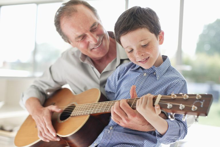Grandfather teaching grandson to play the guitar