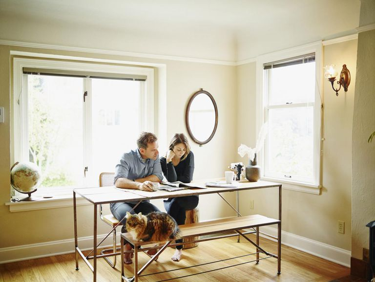 Couple at table in home reading newspaper together