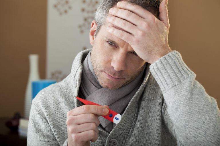 Man taking his temperature at home