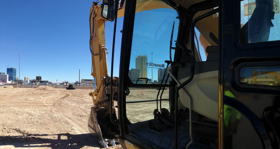 An excavator at Dig This with the buildings of the Las Vegas strip in the background