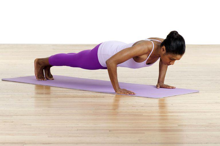 Woman practising push-ups on exercise mat