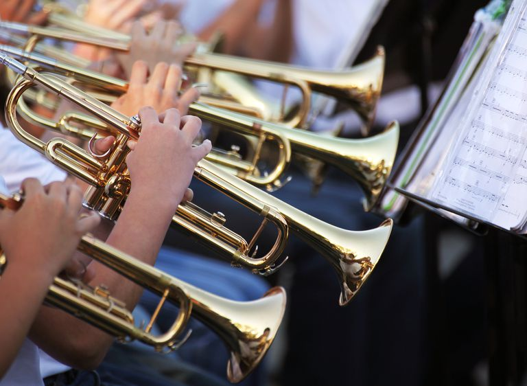 Multiple trumpet players reading sheet music