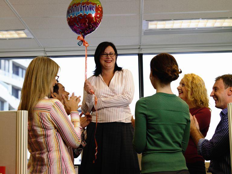 Colleagues applauding businesswoman holding 'congratulations' balloon
