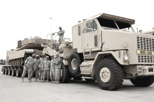 military posed in front of truck