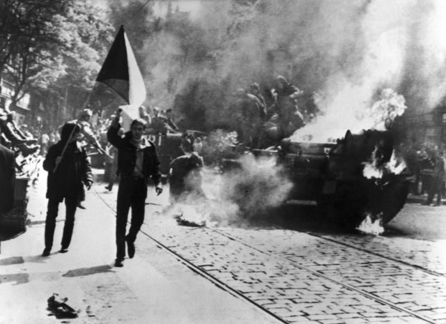 Czechoslovaks carry their national flag past a burning tank in Prague.