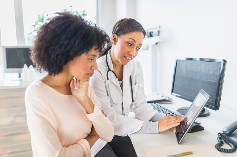 African American doctor and patient talking in office.