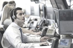 Business man working at desk on multiple monitors tracking data and stocks while wearing headset.