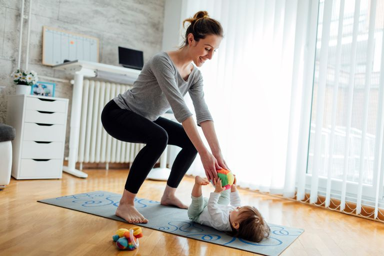 mom doing squats while playing with baby laying on her exercise mat