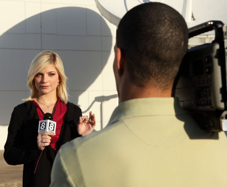 A photo of a TV news reporter speaking into a camera.