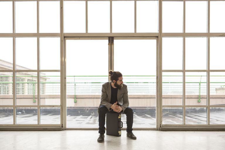 Italian businessman waiting in front of building