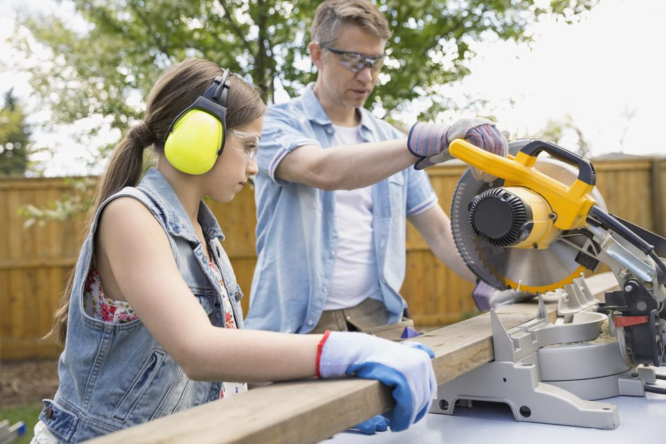 Father and daughter using miter saw