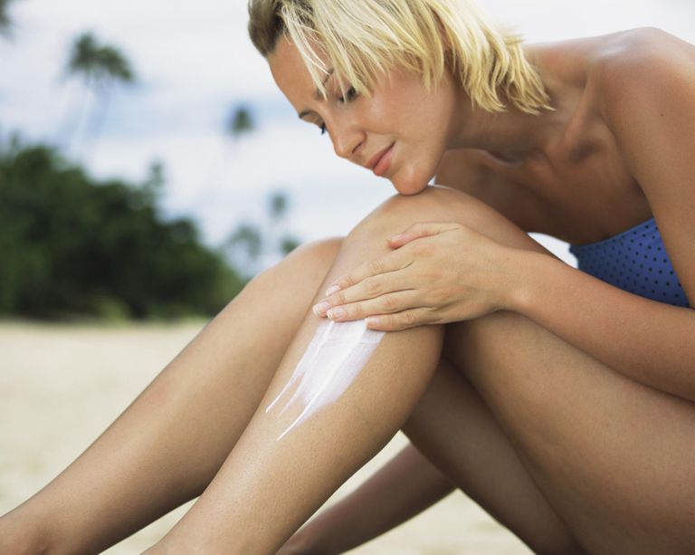 Woman applying sunscreen lotion to leg