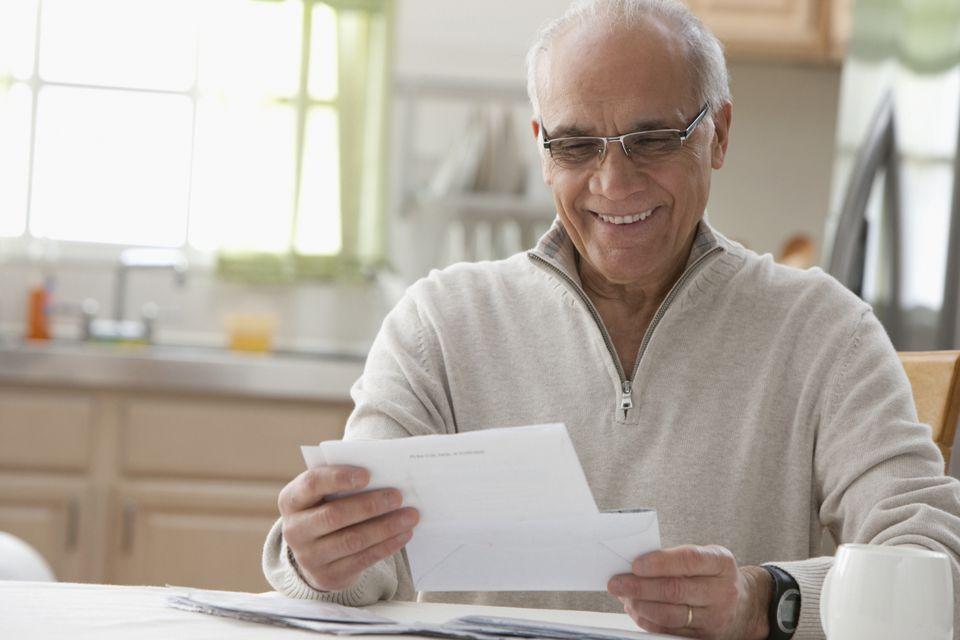 Hispanic man reading mail in kitchen