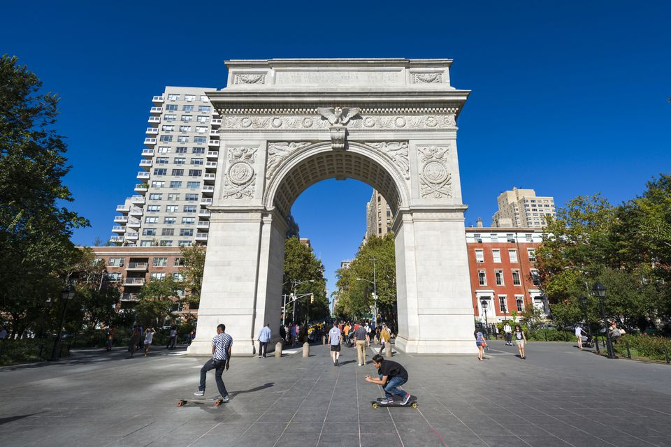 Two skateboarders film and photograph while riding in front of Washington Square Arch,Washington Square Park Arch, New York, New York, USA