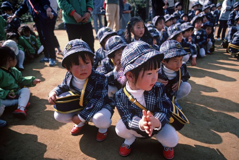Korean children sitting on the ground in school uniforms