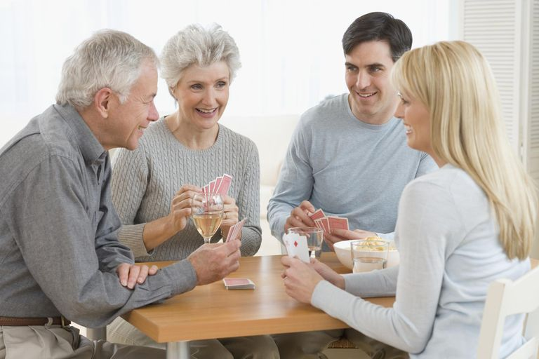 Senior couple and young couple playing cards