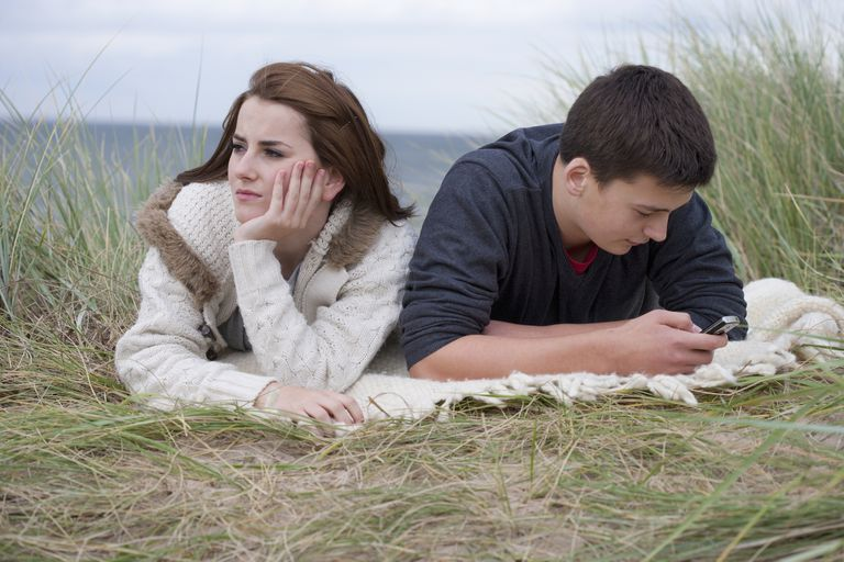Teenage girl and boy lying on blanket while boy texts on cellphone