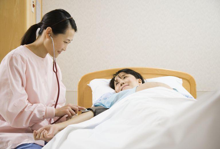 Female nurse checking blood pressure of pregnant woman