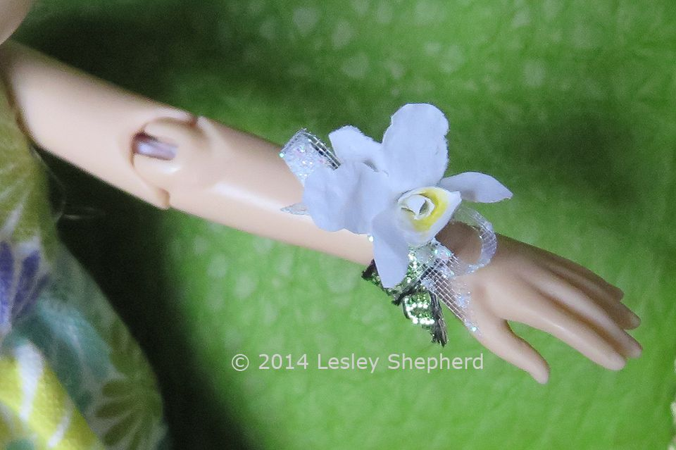 A wrist corsage for a dollhouse doll with a miniature cattleya orchid made from paper.
