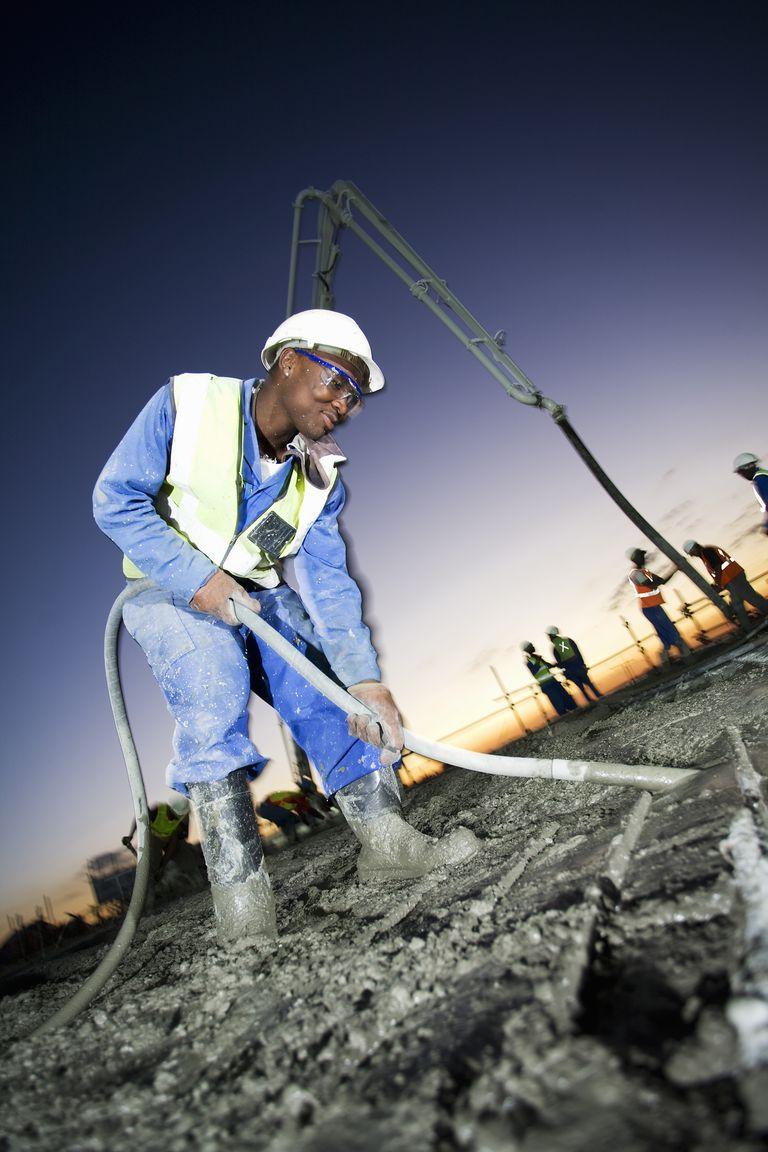 Construction worker using poker vibrator, constructing bridge at dusk, N14 highway, Lanseria, Gauteng Province, South Africa