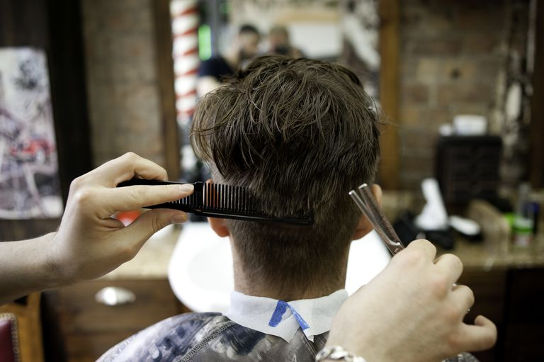 Rear view of young man in barbershop having haircut