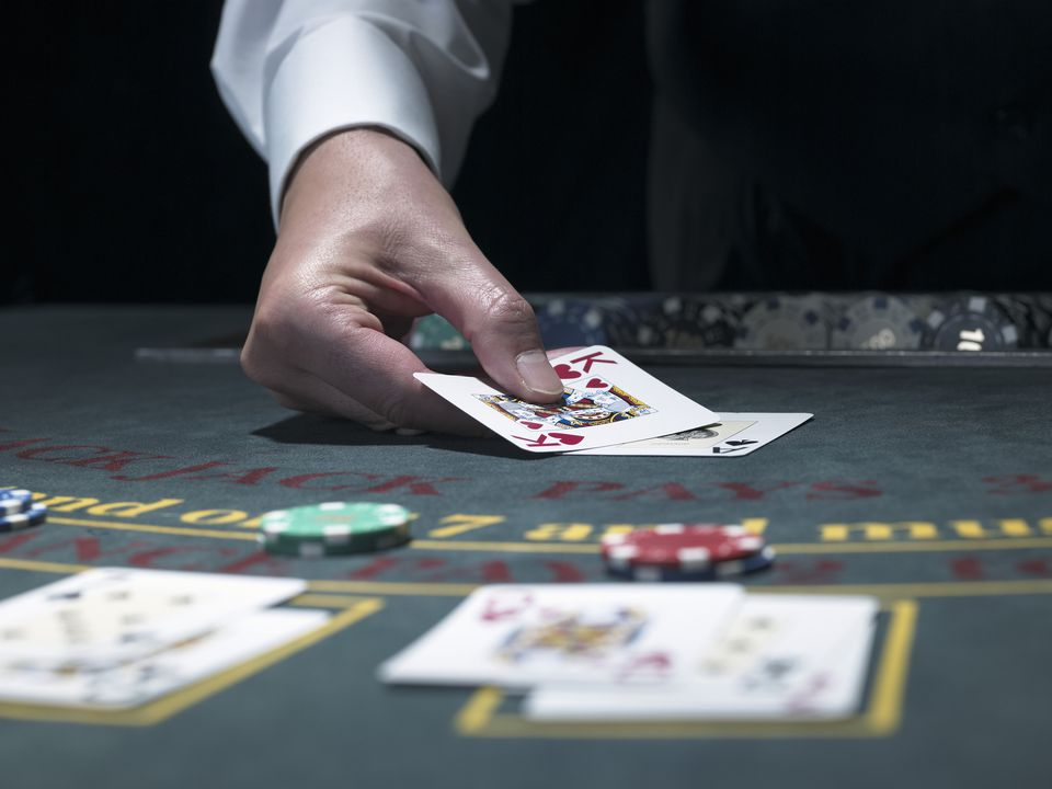 Male croupier turning over card at Blackjack table, close-up
