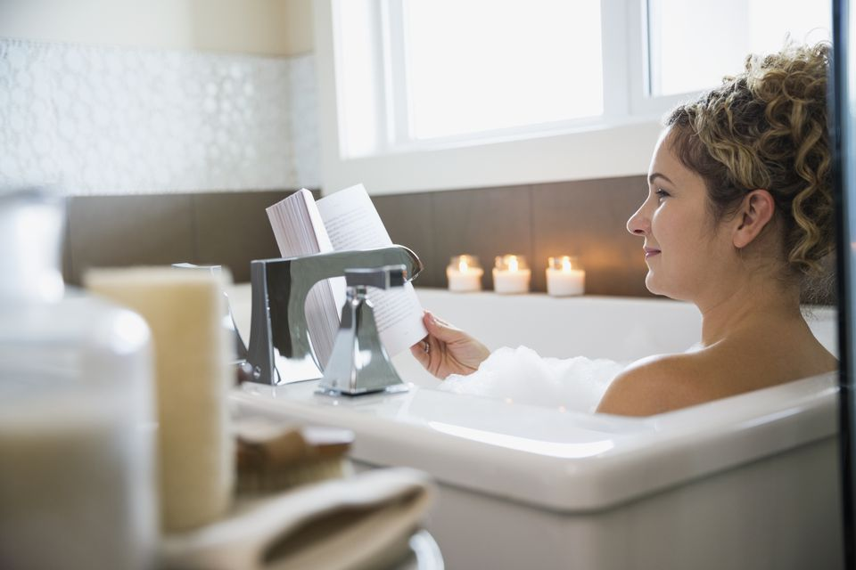 Mature woman reading book in bathtub