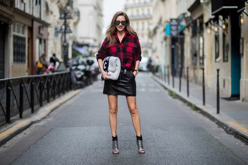 Street style woman in plaid shirt and leather skirt