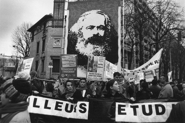 French workers strike for better wages in 1990 and carry a banner with an image of Karl Marx, showing the lasting importance of his ideas and activism. Learn about Marxist sociology here.