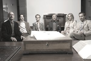 Group of men and women seated in front of desk, envelopes on desk