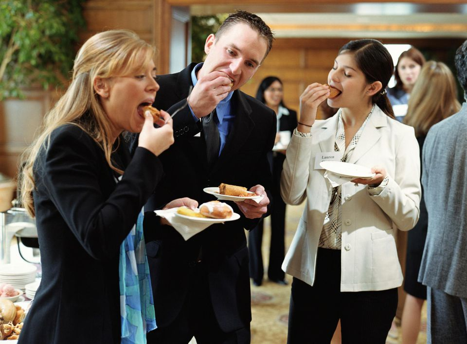 Young business professionals eating food at conference buffet