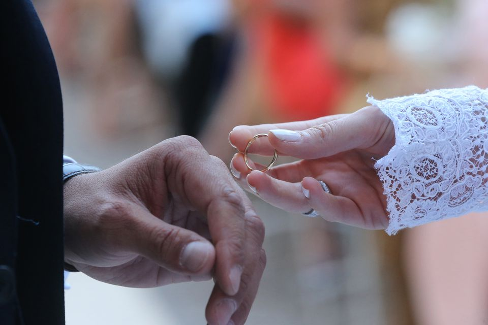 Close up of a couple exchanging wedding rings during a marriage ceremony