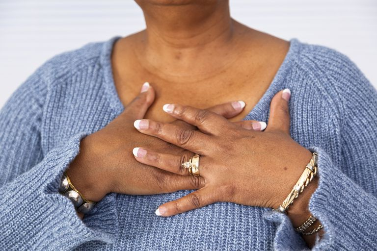Senior African descent woman clutches chest in pain.