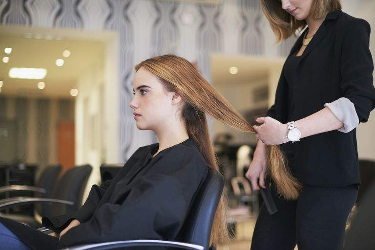 Hairdresser preparing to cut customers long hair in salon