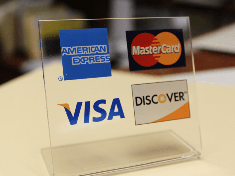 Retail placard with Visa, MasterCard, Discover, and American Express logos