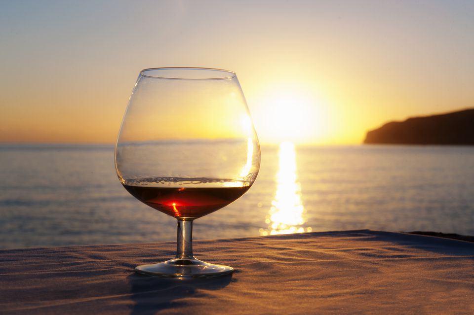 Sunset over sea with brandy glass on table, Mallorca, Spain