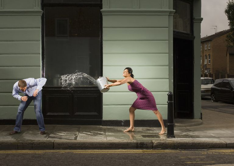 woman throwing bucket of water on man on street
