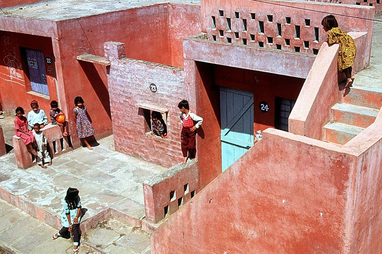 close-up of children within multi-level, pink-colored masonry spaces
