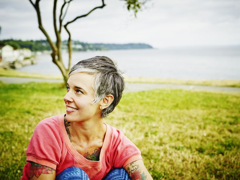 Smiling woman sitting in park before run