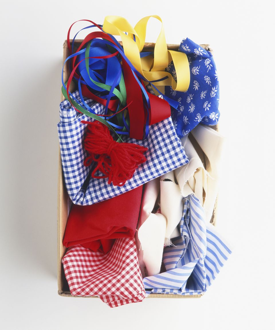 Shoebox containing spare bits of coloured yarn, coloured ribbons, scraps of plain and patterned fabric, view from above
