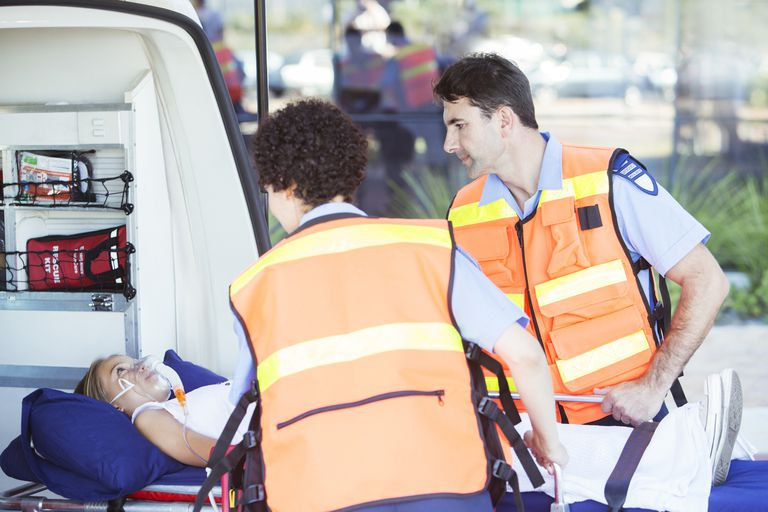 Paramedics examining patient on stretcher