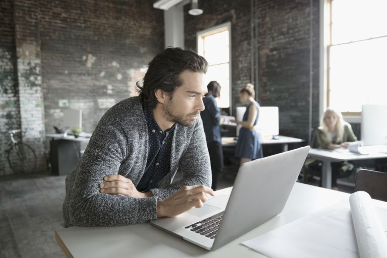 Focused male working at laptop in open plan office