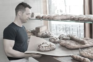 male bakery owner holds rustic bread