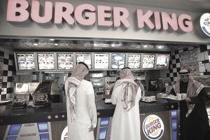 Two Saudi tourists and a Kuwaiti eating at Burger King, Kuwait City.